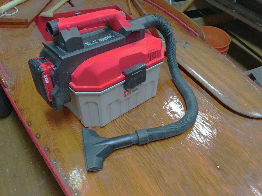 The vacuum carries a crevice nozzle in the handle and a battery on one end. When not in use, the wide nozzle clips into a recess in the other end and the hose snaps into hollows around the whole case.