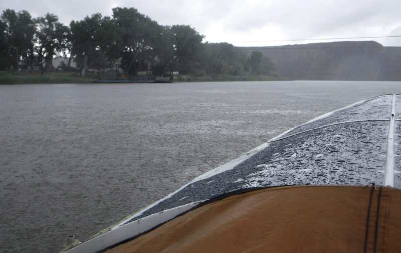 With water above and water below, I cowered under my spray skirt trying to stay dry. I approached the Virgelle Ferry, here idle on the far bank, and passed beneath the overhead cable it travels along, just visible through the rain.