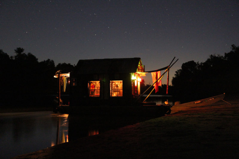 With the skiff pulled ashore and the shantyboat tethered to the banks, our home for the night is bathed in the warm glow of kerosene lanterns.
