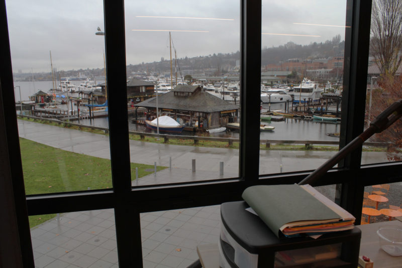 Windows on the south side of the building provide a view of the old boat shop, nearest, and CWB. Lake Union extends to the north at the far left.