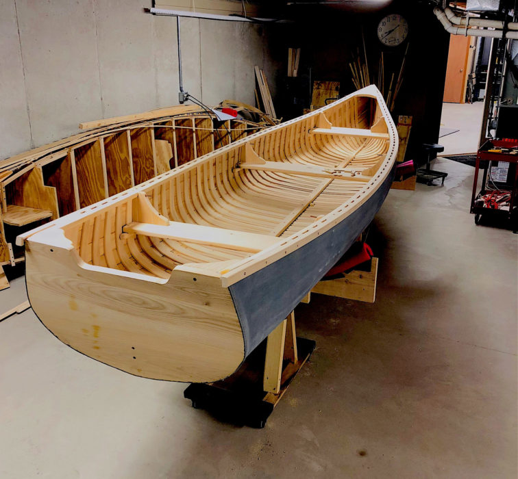 The filler that's used to smooth the canvas skin takes weeks to dry. Before it was applied, the canvas at the stern was trimmed, tucked under, and sealed with a bit of caulking before being tacked to the transom.