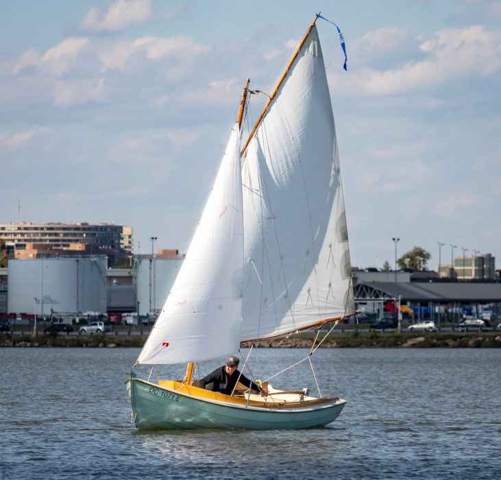 "The hull, according to the designer, ""has a hint of Cape Cod catboat in her, shallower and a bit beamier than a modern row/sail design without being anywhere near as extreme as a true Cape cat. The extra beam increases her initial stability."""