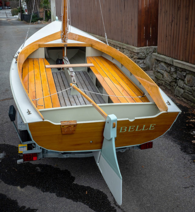 The removable rowing thwart is shown here in place, spanning the centerboard trunk. A bulkhead just forward of the transom serves as a backrest and creates an out-of-the-way space for stowing an outboard. The 8'-long cockpit and berth-wide benches offer, with the addition of a boom tent, overnight accommodations.