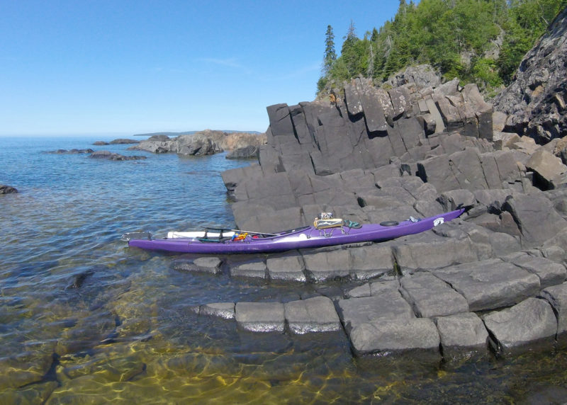 My rugged kayak rested on the rocks at the only accessible stopping place during this late afternoon paddling along wild St. Ignace Island's southwestern side. Spindly pines, lichen-spattered basalt, and clean, clear water were the norm in the north reaches of the lake.