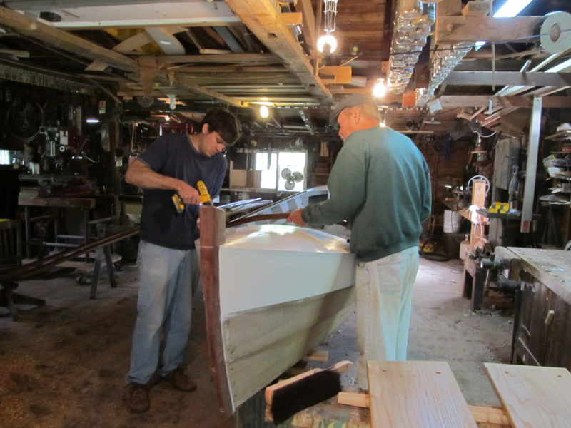 Nick and Daniel install trim as the boat nears completion in the shop that father and son share.