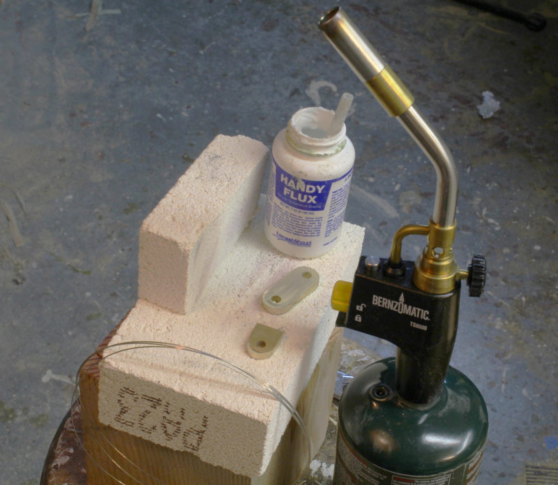 The materials for silver soldering include silver-solder wire, a firebrick work surface, flux and a torch. The TS 8000 is attached to a propane 1-lb bottle, the kind I use for some of my camp stoves. The more slender 14.1-oz propane bottles also work. The firebrick is very soft and it's quite easy to saw of a bit of the end to serve as a backstop.