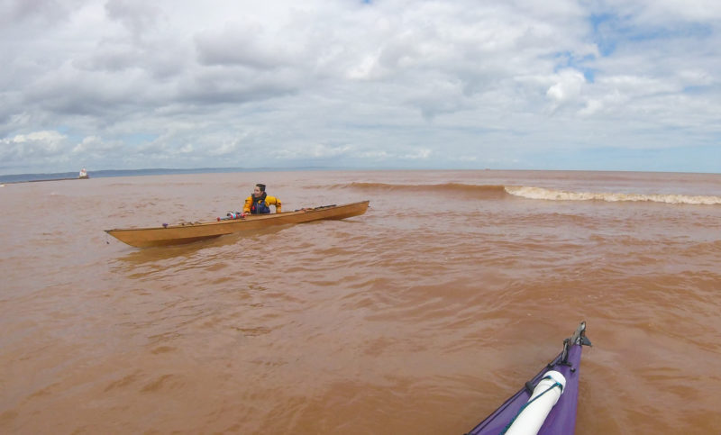 Sophie waded her boat in ahead of surf to a thin strip of beach at Wisconsin Point. It was the last Wisconsin beach we could land on before passing Superior Entry Light, here in the distance just above the kayak's bow, and entering Minnesota. The reddish hue of the water is our last reminder that we were still in Wisconsin—where the clay soil dissolves into the water.