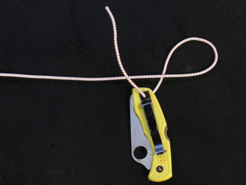 To tie a small bungee tether to an important bit of gear, start with the underhand loop, as usual, and then thread the cord through the item at the start of the second loop.