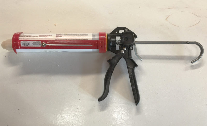 The foil-puncturing tool pivots in and out of a recess in the red frame. The cartridge-tip cutter is the circular hole to the right of the spring.