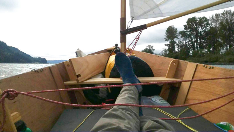 Lying supine in the stern is the most relaxing position for me and the most stable for sailing. Removing the rowing thwart and setting it in the bow gives me more room to stretch out. Cloud cover kept the sun off me while I sailed toward the east end of Puget Island after leaving Cathlamet.