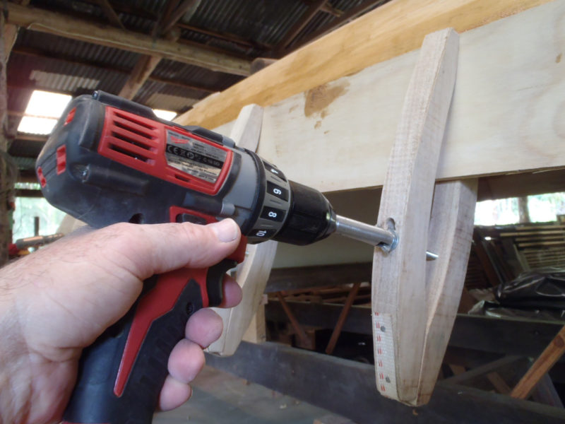 Peter's homemade planking clamps are tightened with wing nuts on bolts. To spin and tighten the wing nuts quickly he put a slot in a piece of steel tube to straddle the wings and put a rod in the other end to fit a cordless drill.