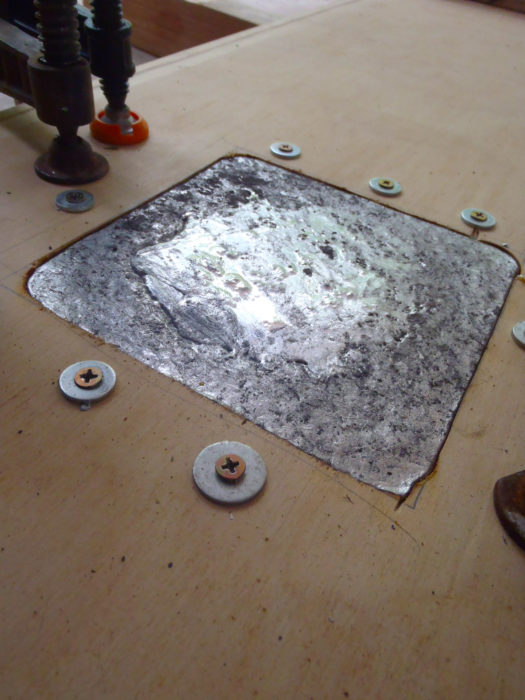 Screws and washers keep molten lead from seeping between layers of plywood that will later be epoxied together and sheathed with fiberglass.