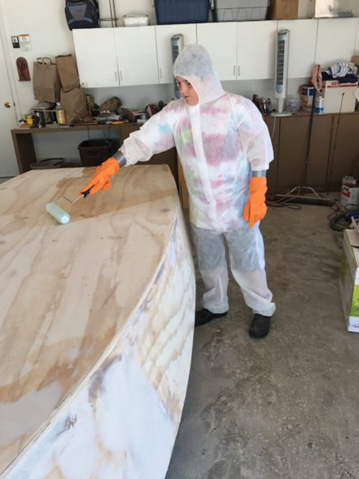 Decked out with protective clothing, Henry can roll epoxy on the hull without ruining his tie-dye T-shirt and shorts.