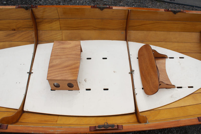 The slots in the center and aft floorboards are for the foot braces, not for the seats, which are held in place by the weight of the rower. The frames are flush with the floorboards in the middle of the boat, providing a place to stretch out.