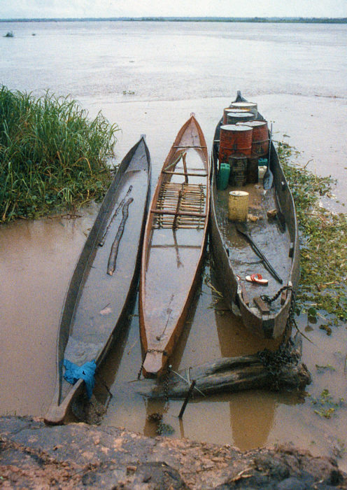 Any port in a storm. FIFTY GOOD ONES and ALICE MAY chained and cabled to a driftwood mooring alongside a bulky freight pirogue on the Kasai River. We had a lot of bailing to do.