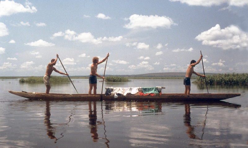 "ALICE MAY was a ""six-man"" pirogue. We—(from left) Ted Cooney, Tom DeVries, and Brent Simpson—are putting our backs into it as the laundry dries. The hardwood paddles are flexible and strong."