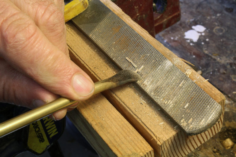 Whatever debris that the file card leaves behind can be forced out by pushing parallel to the grooves with metal softer than the files hardened hi-carbon steel. Here a flattened brass rod does the work, here on a 4-in-1 rasp and file.
