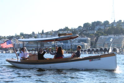 white motor launch on lake union with four passengers